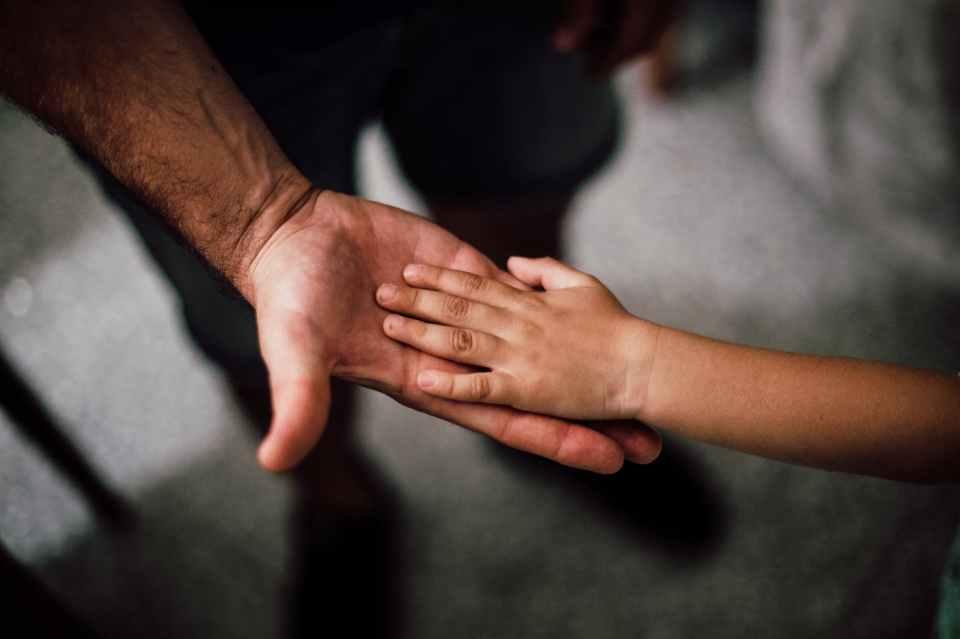 Barnehånd i voksen hånd